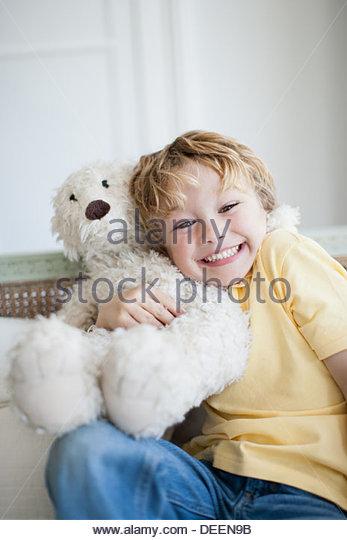 Smiling boy hugging teddy bear - Stock Image