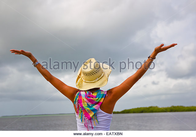 A woman wearing a colorful scarf reaches for the sky. - Stock Image