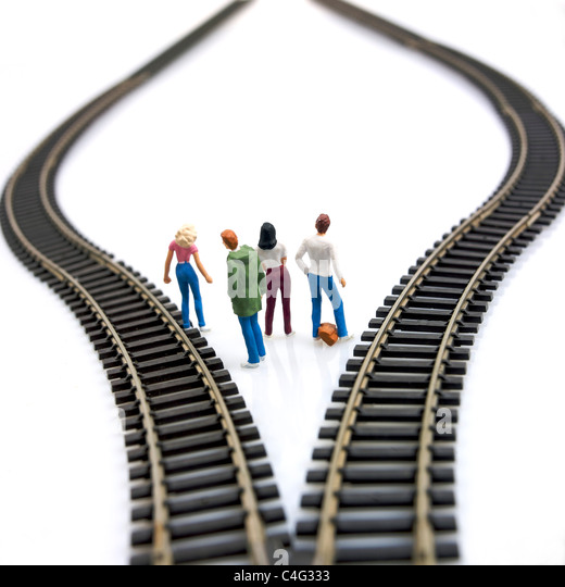 Young people figurines between two tracks leading into different directions, symbolic image for making decisions. - Stock Image