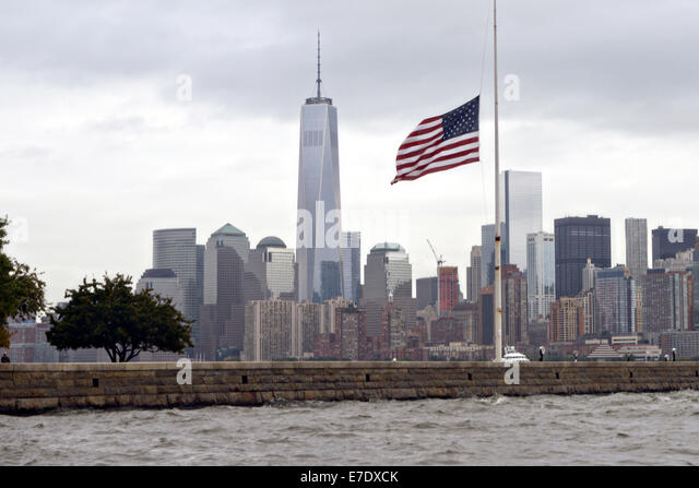 The American flag on Ellis Island at half-staff on a cloudy day with the Freedom Tower and skyline of Manhattan - Stock Image