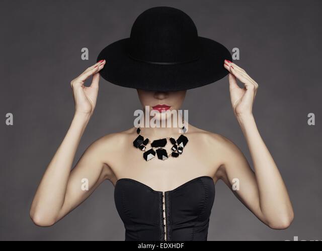 Fashion photo of beautiful lady in elegant black hat - Stock Image