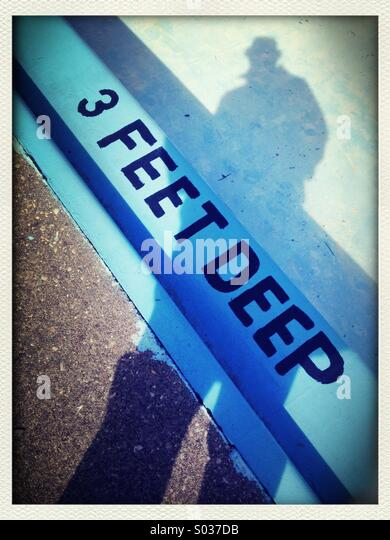 Shadow of person at edge of empty swimming pool  '3 feet deep' - Stock Image