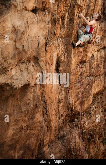 Caucasian male climber leading a trad line up a sandstone cliff in Badami, India. - Stock-Bilder
