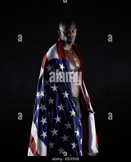 Portrait of Afro-American athlete wrapped in USA flag against black background. Bodybuilder with American flag in - Stock Image
