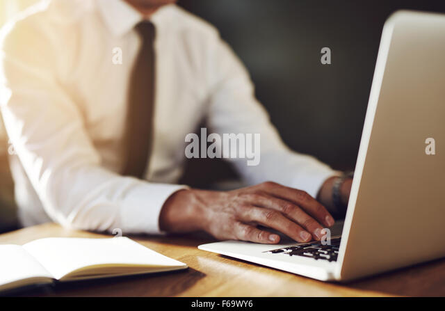 Close up of hands writing at laptop, business concept, white shirt and tie - Stock-Bilder