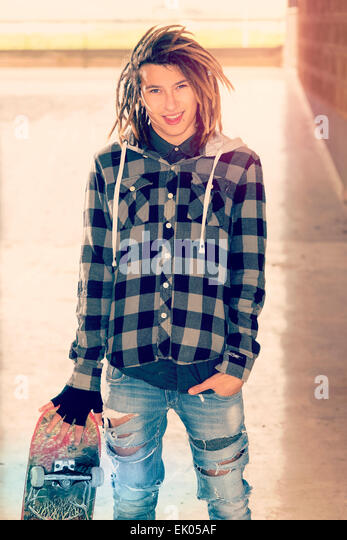 portrait of young guy  with skateboard and rasta hair in a lifestyle concept warm filter applied - Stock-Bilder