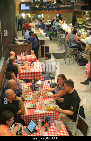 New Jersey Newark Newark Liberty International Airport EWR terminal concourse gate area restaurant tables - Stock Image