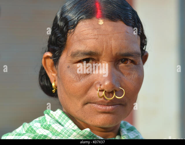 Mature Indian Adivasi woman with red sindoor, three golden nose rings and tribal earrings. - Stock Image