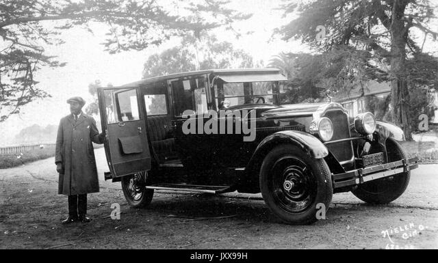 Landscape shot of Packard car, African American man holding the back door open wearing a hat and jacket, outdoors, - Stock Image