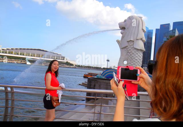 Singapore Singapore River Marina Bay Merlion Park Asian woman posing taking picture camera - Stock Image