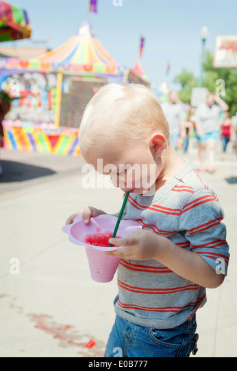 Male toddler concentrating on juice drink at funfair - Stock Image