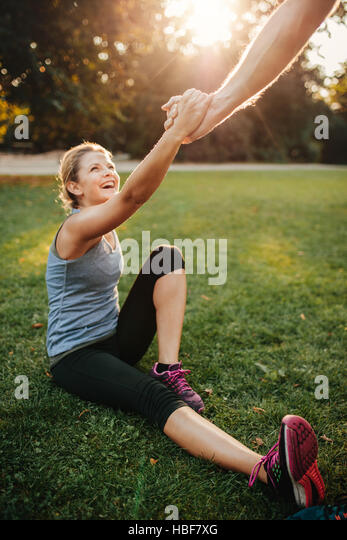 Shot of man helping woman to stand up. Healthy young couple at park exercising together. - Stock Image