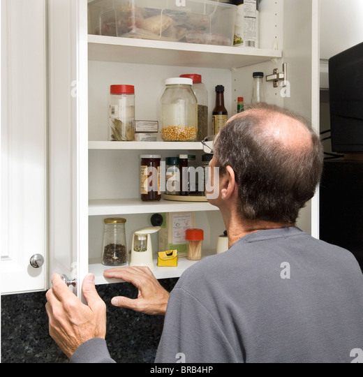 man standing in front of kitchen cabinet with little food - Stock Image