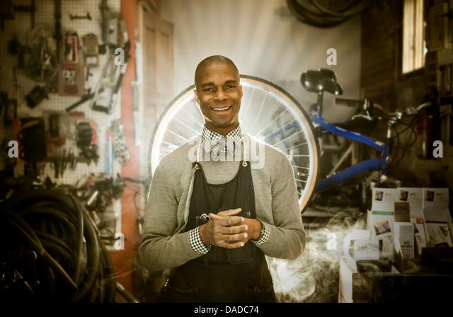Bike mechanic against backdrop of heavenly rays of light - Stock Image