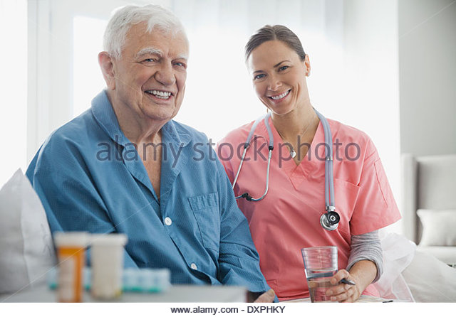 Portrait of home care nurse sitting with senior patient - Stock Image