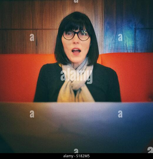 Woman holding menu and looking surprised - Stock Image
