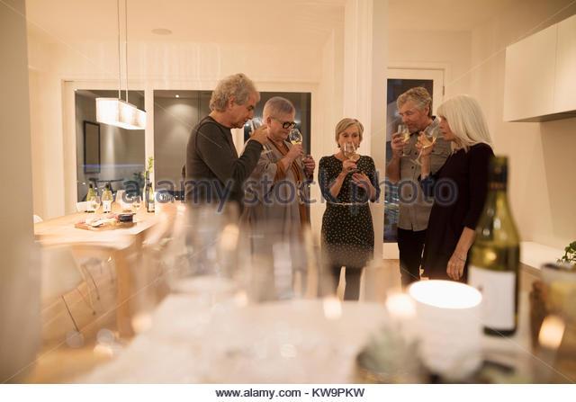 Senior couple friends smelling wine,enjoying wine tasting party - Stock Image