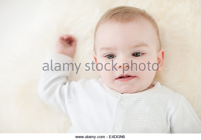 Closeup of smiling baby laying on rug - Stock Image