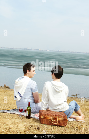 Vertical shot of a homosexual couple on a picnic at lakeside - Stock-Bilder