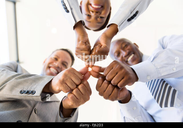 underneath view co-workers with thumbs joined together - Stock Image