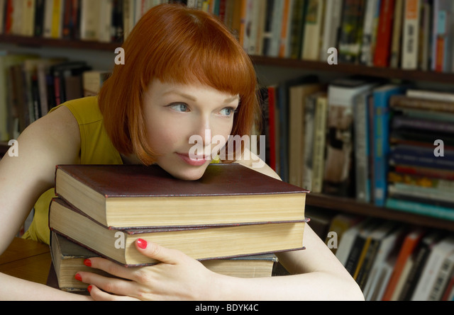woman leaning on pile of books - Stock Image