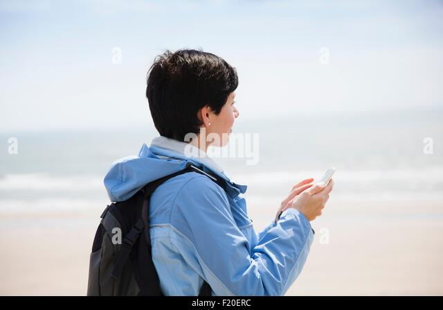 Mid adult woman texting on smartphone from beach whilst looking out to sea - Stock Image
