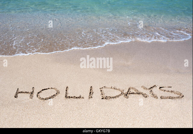 Word Holidays sketched on a tropical beach in the golden sand - Stock Image