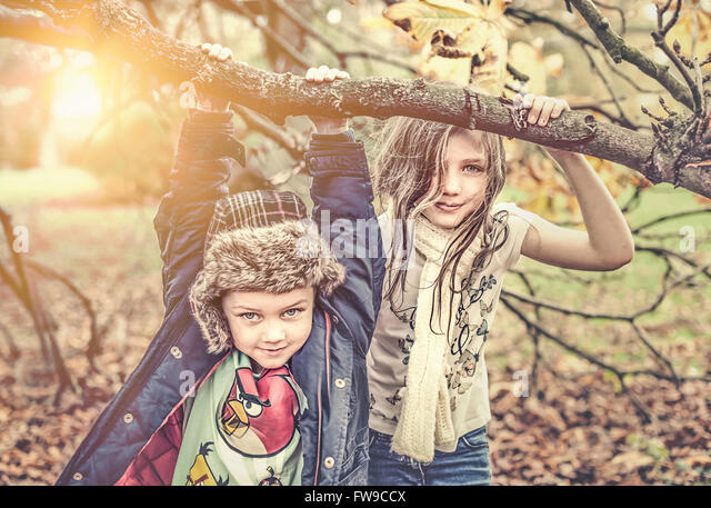 two children playing in autumn park in sunny day - Stock Image