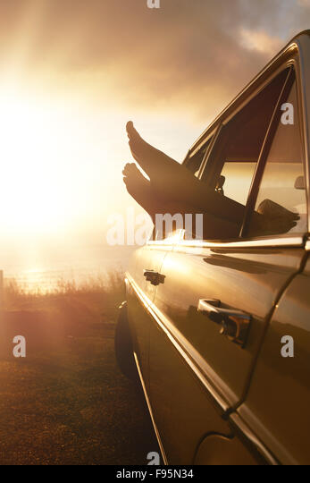 Summer holidays road trip concept. Woman hanging her legs out of car window  at sunset. - Stock Image