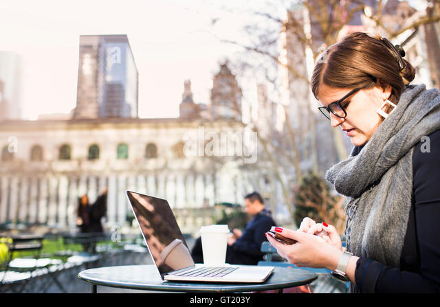 Businesswoman using phone while sitting at table in Bryant Park - Stock-Bilder