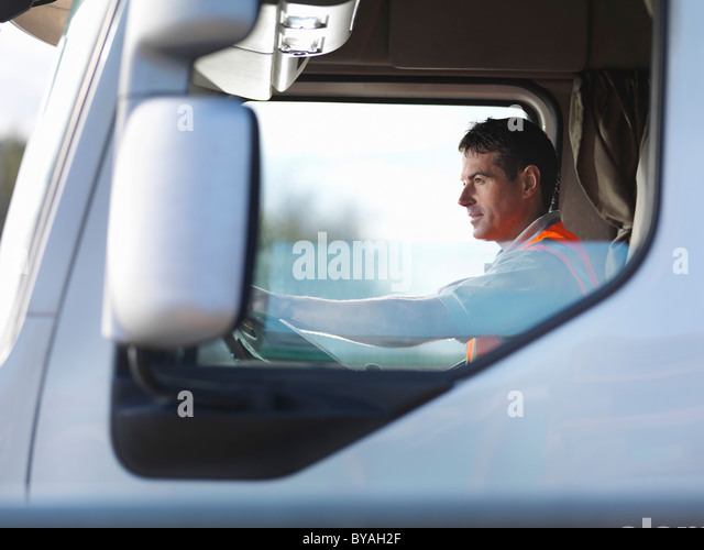 Truck driver in truck cab - Stock Image