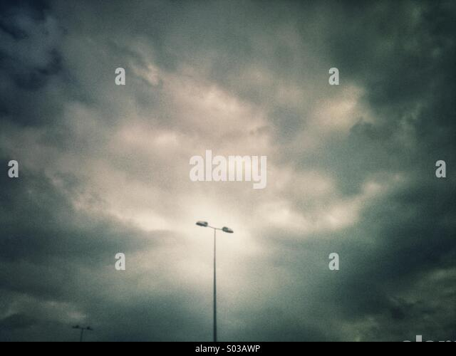 Single motorway overhead light with dark clouds behind. Grunge effect applied. - Stock Image