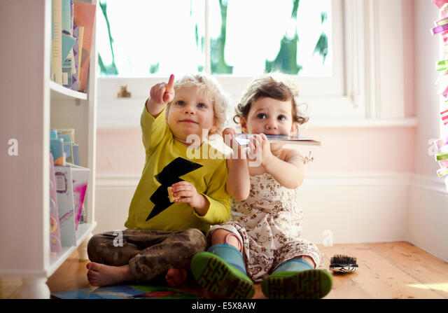 Female and male toddler friends pointing and looking up - Stock-Bilder