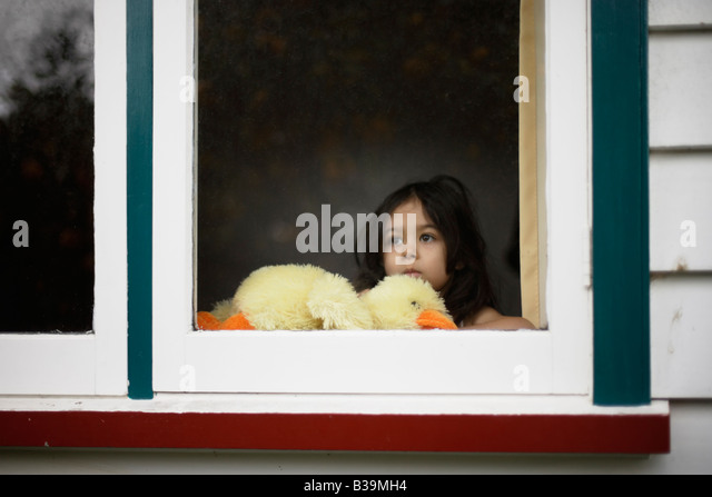 Girl aged 5 looks out window holding soft toy duck - Stock Image