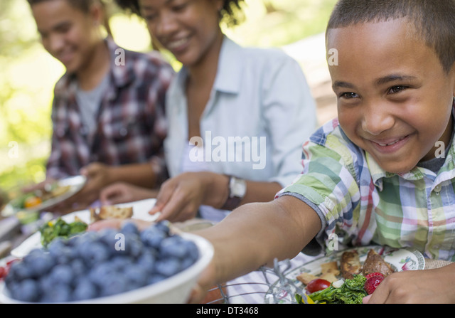 A family picnic in a shady woodland Adults and children sitting at a table - Stock-Bilder