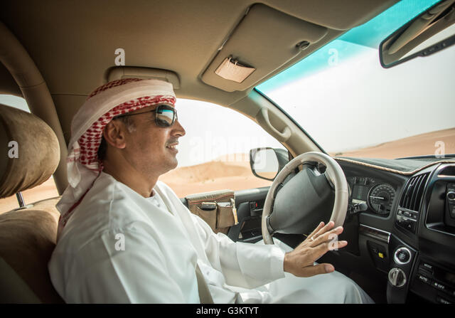 Middle eastern man wearing traditional clothes driving off road vehicle in desert, Dubai, United Arab Emirates - Stock-Bilder