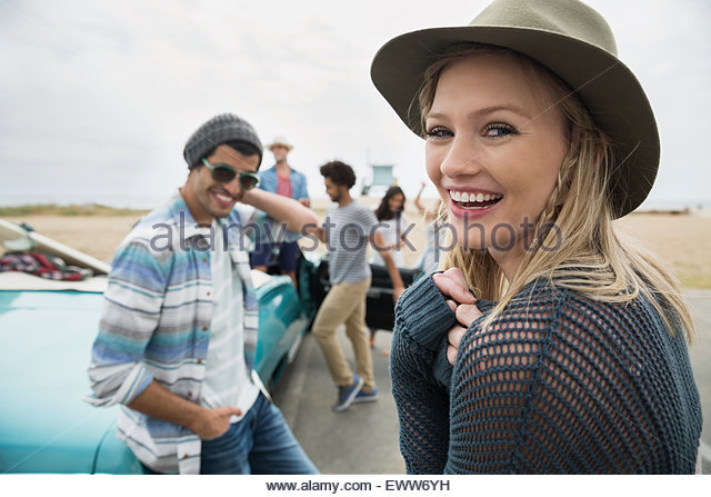 Portrait smiling young woman hanging out friends beach - Stock Image
