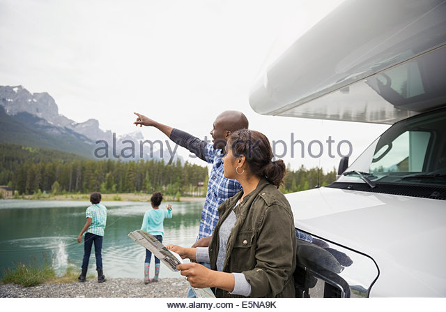 Family with map at RV near lake - Stock Image