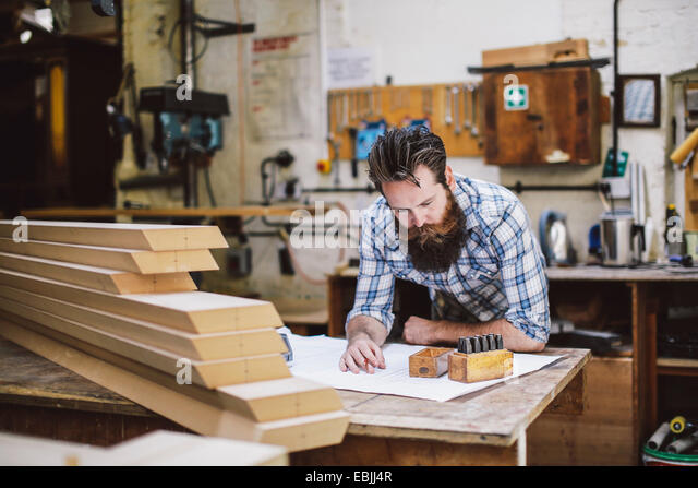 Mid adult craftsman looking down at blueprint in organ workshop - Stock Image