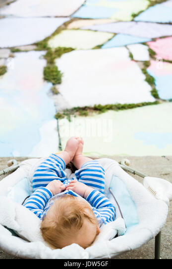 High angle view of baby sitting in bouncer chair - Stock-Bilder