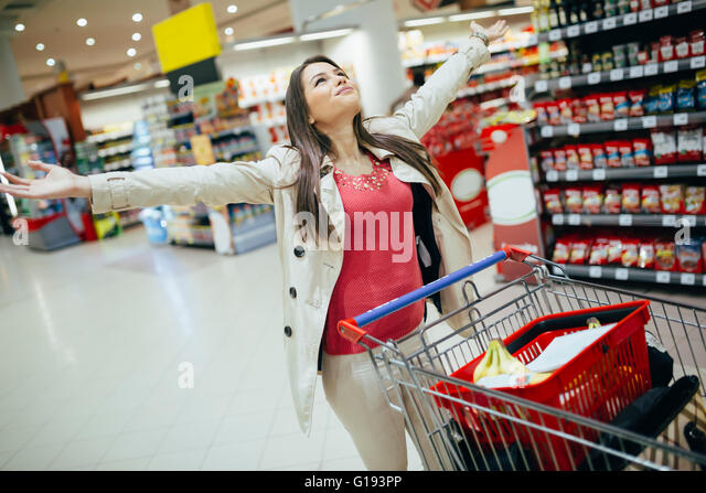 Woman happy when shopping in supermarket - Stock Image