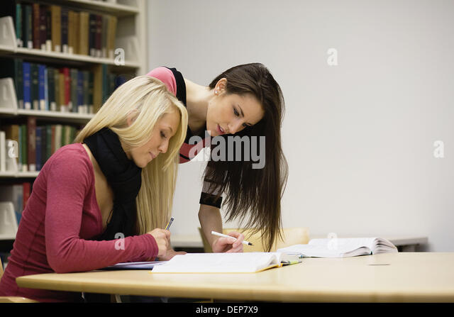 Two young women studying together in a university library - Stock Image