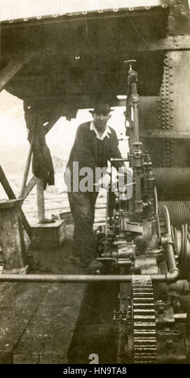 Antique c1920 photograph, man standing near steam-powered machinery USA. - Stock Image