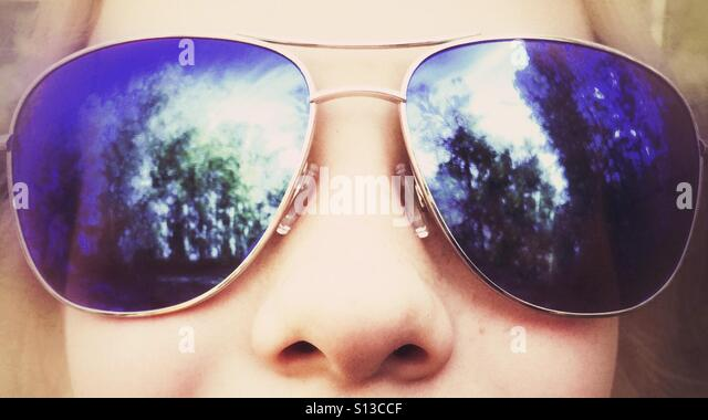 Oversize aviator sunglasses reflecting trees on a child. - Stock Image