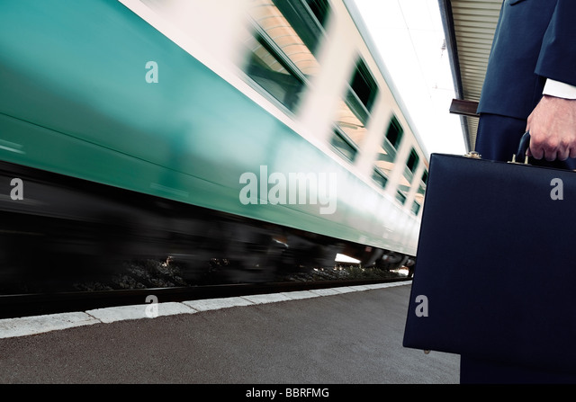 Commuter Standing on a Train Station Platform as a Train Goes Past Low Section - Stock-Bilder