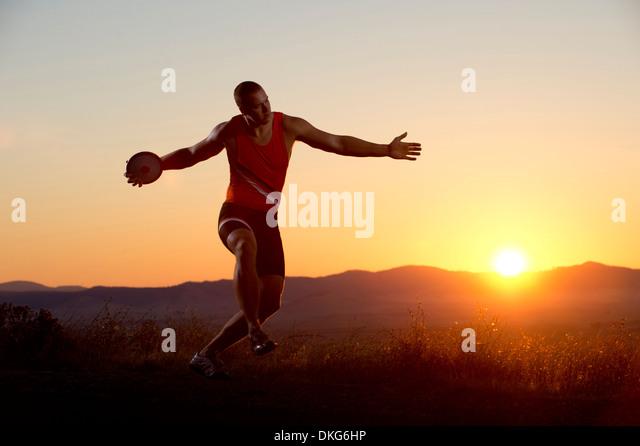 Young man preparing to throwing discus at sunset - Stock Image