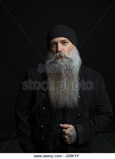 Portrait confident hipster man with long gray beard against black background - Stock Image