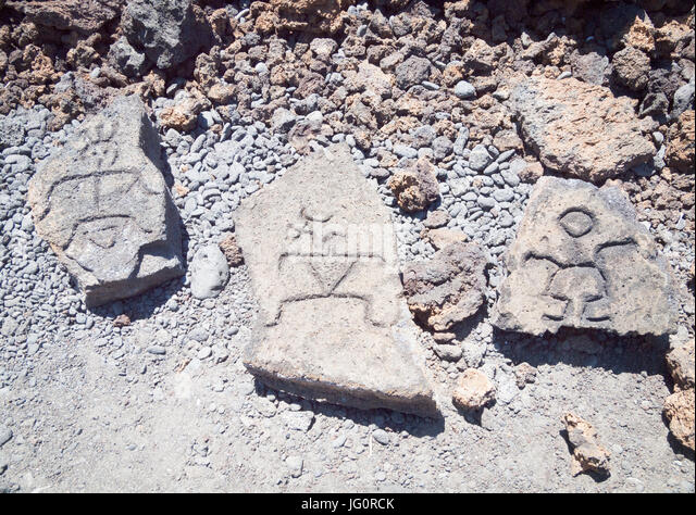 Petroglyphs carved in lava rock at Puako Petroglyph Archaeological Park near Waimea, Big Island, Hawai'i (Hawaii). - Stock Image