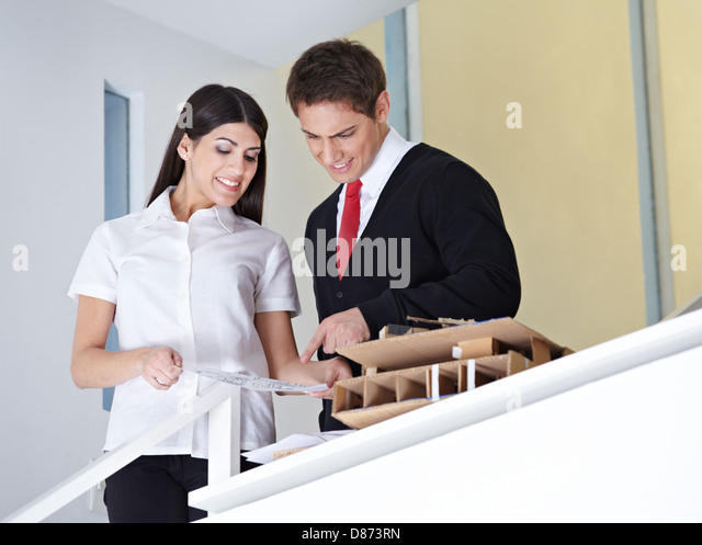 Two architects in the office discussing a construction drawing - Stock Image