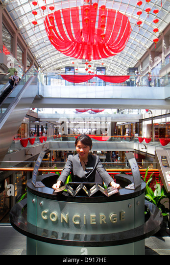 Singapore The Shoppes at Marina Bay Sands shops shopping Asian woman concierge service - Stock Image